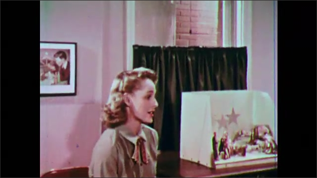 1950s: Little girl hangs star in nativity scene.  Woman turns little girl around.  Woman speaks and sits down.