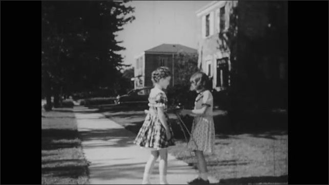 1950s: Girl talks. Girls run toward each other and jump rope together.