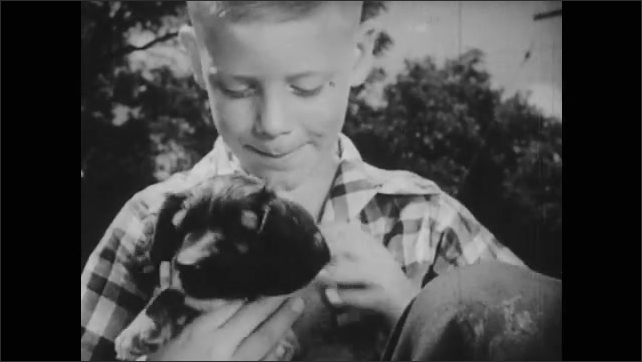 1950s: Boy picks up puppy and pets it. Boy looks off to side and closes his eyes.