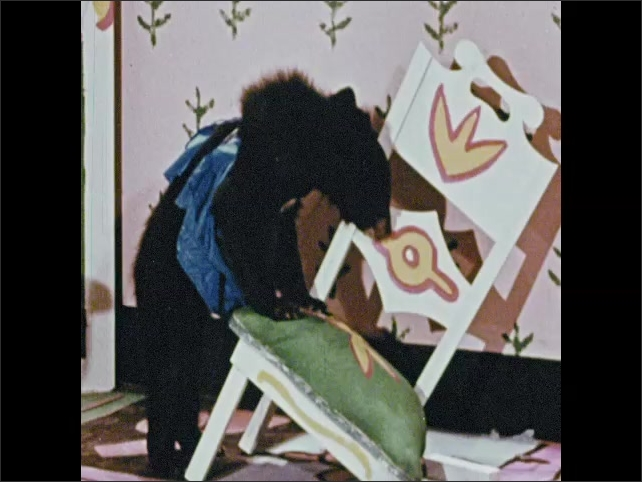 1950s: Mother bear sits in medium sized chair in fairytale house. Baby bear looks at broken small chair. Father bear eats porridge from large sized bowl at table.