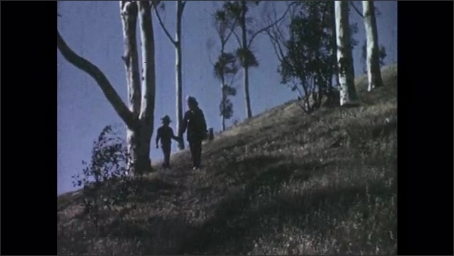 1950s: boy and girl in cowboy hats hold hands, walk down path on hill past bare trees and point with fingers as bushes blow in wind.