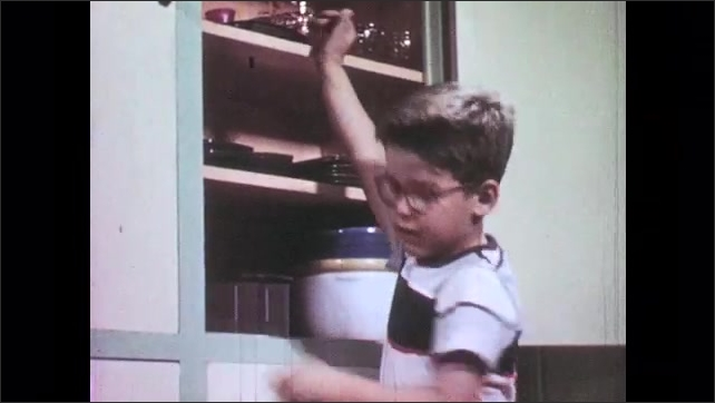 1950s: boy and girl carry basket across backyard and hang laundry on clothesline with clothespins. boy places plate on cabinet shelf. girl washes in kitchen sink as boy plays with toy car on counter.