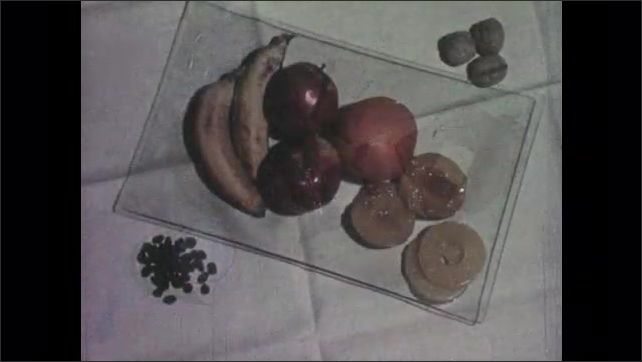 1950s: carrots, peas, and potatoes sit on glass. milk, beans, fish and toast on white cloth. bananas, apples, oranges, walnuts, pineapples on table. hands serve plate of food to boy with glasses.