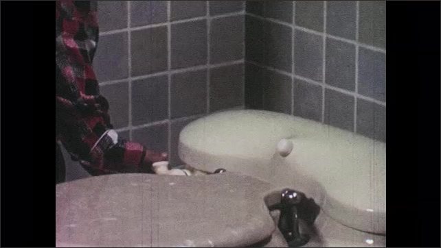 1950s: boy enters bathroom, closes door, flushes toilet with lid down and washes hands with soap in sink under faucet.