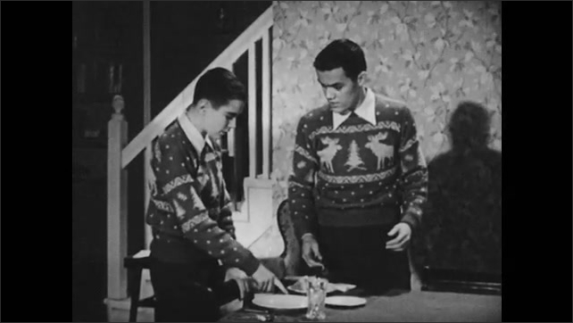 1950s: older brother explaining table manners as well as silver wear and plate placement to younger brother