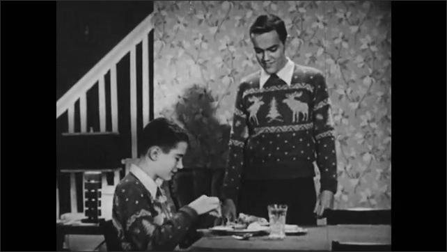 1950s: younger brother holding silver wear wrong and is corrected