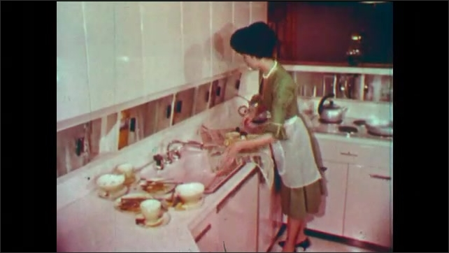 1950s: Woman scrapes food from pot at kitchen counter. Woman grimaces. Woman dumps coffee grounds. Woman gathers newspaper around garbage and lifts. Garbage spills onto kitchen counter.