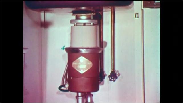1950s: Garbage disposal under sink. Hand closes cabinet door.