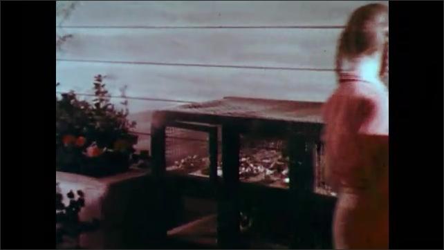 1950s: Children speak and walk away.  Hamster falls out of open cage door.