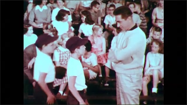 1950s: Baseball game.  Player calls time out.  Umpire.  Players talk to coach.  Spectators.