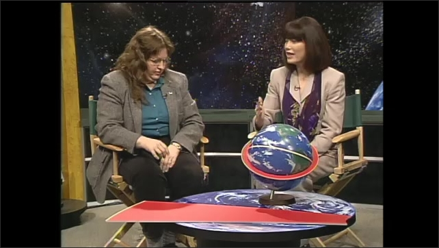 1990s: Women sit in TV studio, Shelley Canright interviews, talks, gestures. Dr. Mary Ann Smith points to red ring around globe to demonstrate low earth orbit, rotates globe, holds up protractor.
