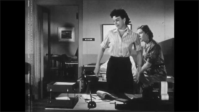 1950s: Three women sit at office desk and converse. Man greet women and enters private office. Two women follow man into office. Man and women converse.