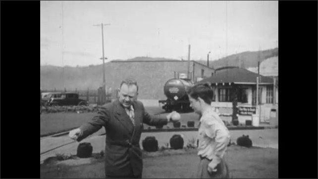 1950s: man in suit ties string to grapefruit and swings golf ball over his head as boy watches in yard near railroad yard with trains.