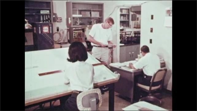 1960s: People work in office.  Man walks into room.  Man lays paper on desk.