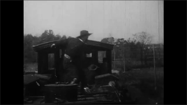1900s: UNITED STATES: robbers fight with train driver. Robbers through man from train. Train stops