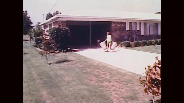 1970s: UNITED STATES: man empties bins into rubbish truck. Lady brings in bins. Men carry trash cans across garden