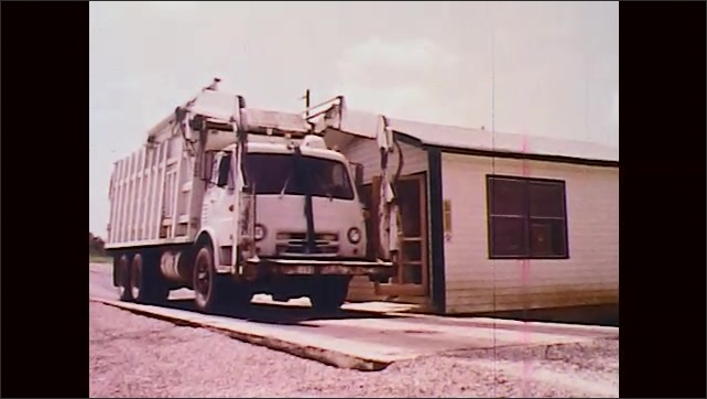 1970s: UNITED STATES: person stands in door of house. Truck arrives at building. Man adjusts scales