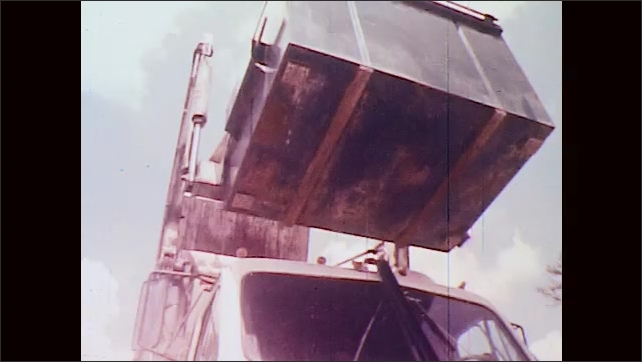 1970s: UNITED STATES: mechanical arms empty container into packer truck