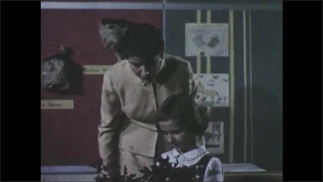 1950s: Girl in classroom shows woman artwork of leaves. Woman talks to girl while holding artwork then hands artwork back to girl and girl leaves.