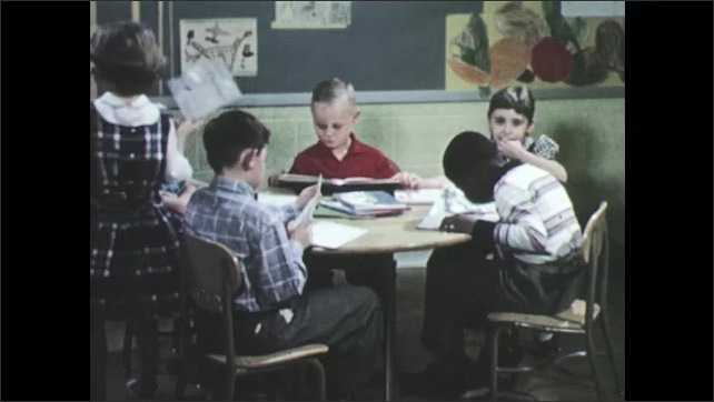 1950s: Group of children sit at round table each with a book, reading and talking. Children sit at desks in classroom with books while woman walks through class talking.