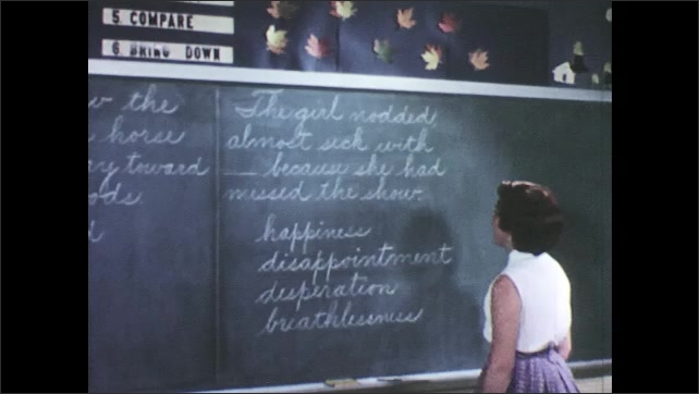 1950s: Boy standing at chalkboard in classroom underlines word on it. Girl stands at chalkboard reading words then underlines one of them.