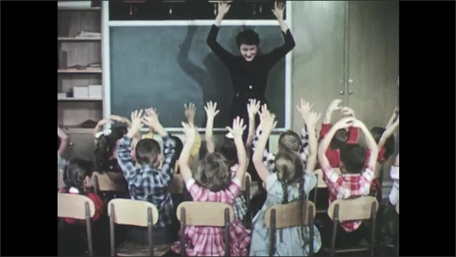 1950s: Boy lays on paper, boy traces outline of boy onto paper. Teacher stands at front of room, moves arms up and down, students sit in seats in front of teacher, mimic her movements.