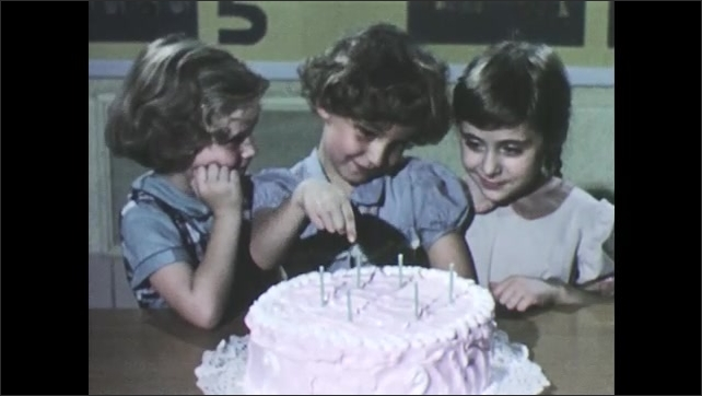 1950s: Girls stand in front of table, one girl waters flower in pot, other girl watches. Three girls look at cake, one girl counts the candles. Two boys sit at table, play with turtle.