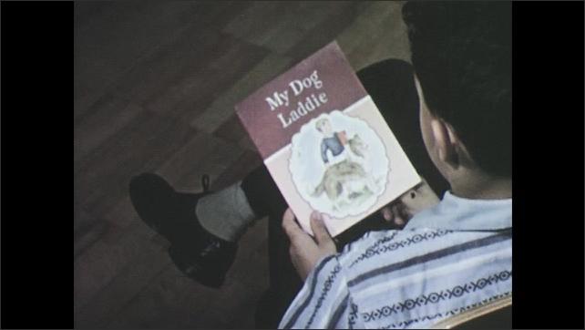 1950s: Boy underlines words in workbook. Boy reads book.