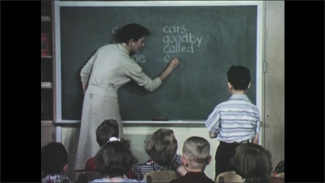 1950s: Woman writes on blackboard, students sit in chairs and watch teacher. Teacher points at words on chalkboard. Boy stands up and talks, woman writes word on board.