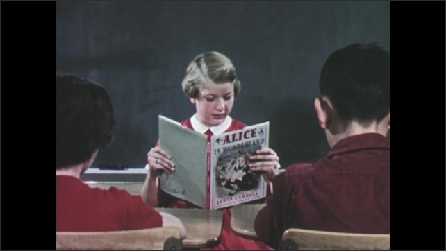 1950s: Girl sits in front of class, reads book. Girl turns book around, shows picture to students.