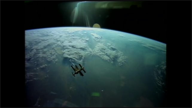 1990s: UNITED STATES: astronaut gets into sleeping bag. Space station above Earth. Astronaut on space walk