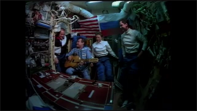 1990s: UNITED STATES: American and Russian astronauts undergo cross cultural training. Astronaut plays guitar in space. Flags on space station wall