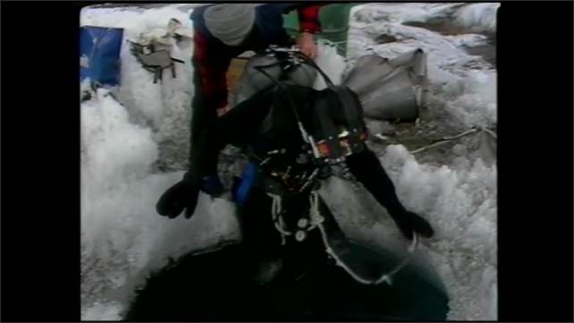1990s: UNITED STATES: scuba divers prepare for ice dive under pack ice.