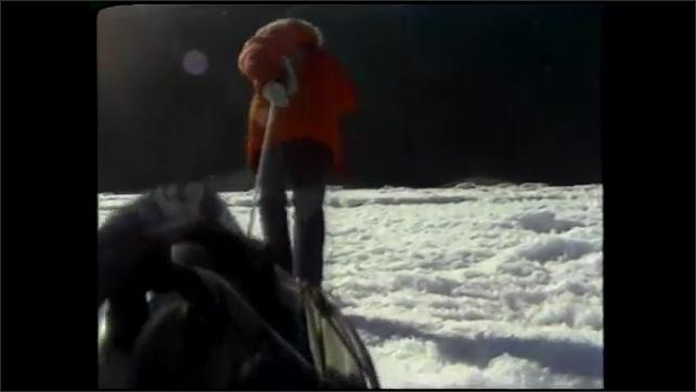 1990s: UNITED STATES: overwintering team in Antarctica. Man pulls pulk across ice.