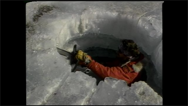 1990s: UNITED STATES: man carries out field research in Antarctica.  Man works in ice hole. Crashed helicopter on ground.
