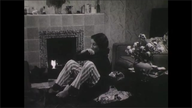 1940s: Girl sits in living room, in front of fireplace, reading book. Woman gets up to tend fire, girl picks up ball of yarn. Girl gets up and hugs woman in chair, then leaves.