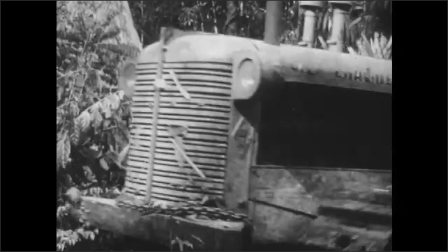 1960s: Tractor drives through forest. Man driving tractor, pulling rock.