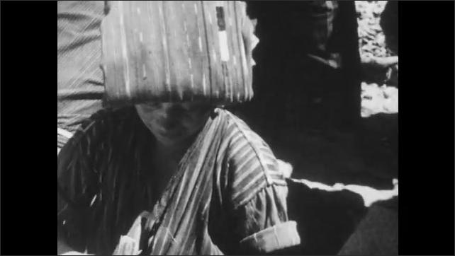 1960s: Woman wraps salt in leaf, tilt up to woman. Tilt up road, people walking.