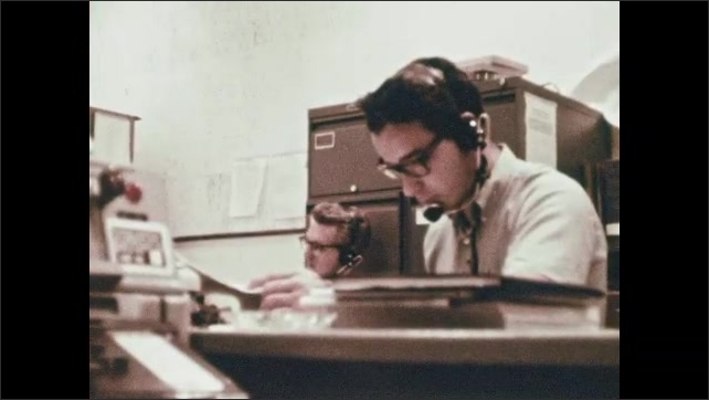 1960s: MEXICO: man listens nervously on headset in office. NASA control center in Mexico. Man listens to beeps on computer