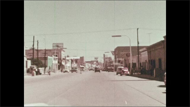 1960s: MEXICO: man directs traffic in street. View of street from car window. Man talks to camera in car