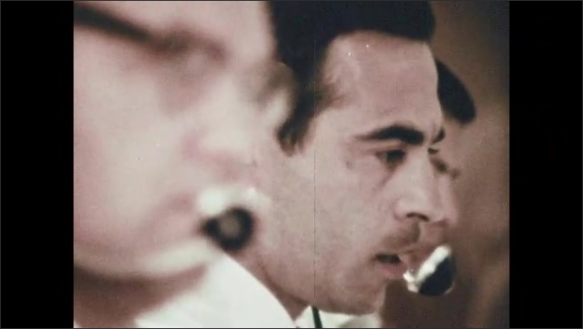 1960s: MEXICO: CAPCOM speaks to crew on spacecraft. Man monitors Agena System. Man with headset