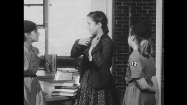 1950s: Woman smiles and watches children. Girl in pigtails dons jacket. Girl scouts talk with girl and leave classroom.