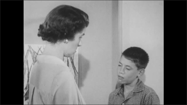 1950s: Woman looks angry and speaks. Boy responds to teacher. Woman and boy talk in classroom.