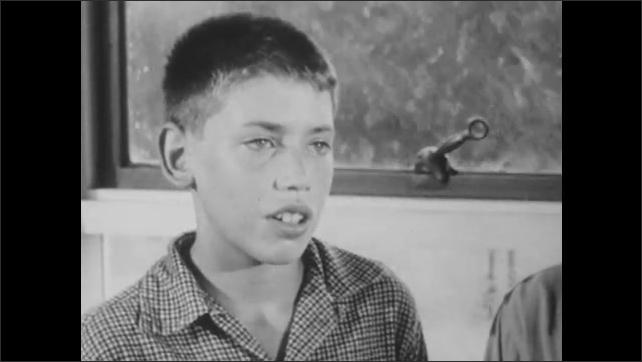1950s: Boy stands near rainy window and talks. Teacher listens and smiles. Rain pounds against windows of classroom.