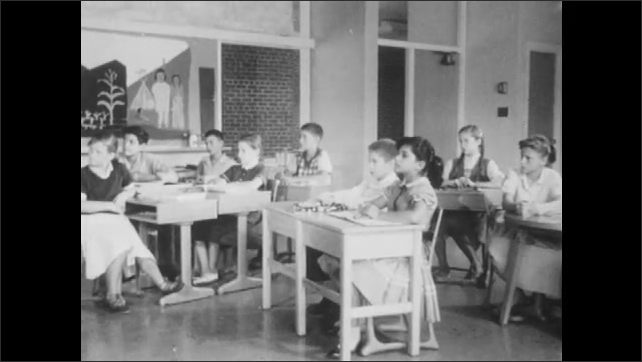 1950s: Boy talks to class in front of chalkboard. Students sit at desks and listen. Boys and girls pat attention.