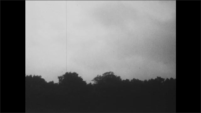 1950s: Rain clouds over tree-line. Rain batters window of classroom.