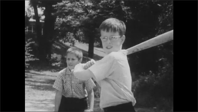 1950s: Boys play baseball on playground. Boys swing bat at home plate.