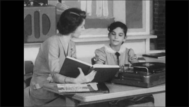 1950s: Girl smiles and speaks. Teacher flips through book and talks with girl. Girl smiles and responds.