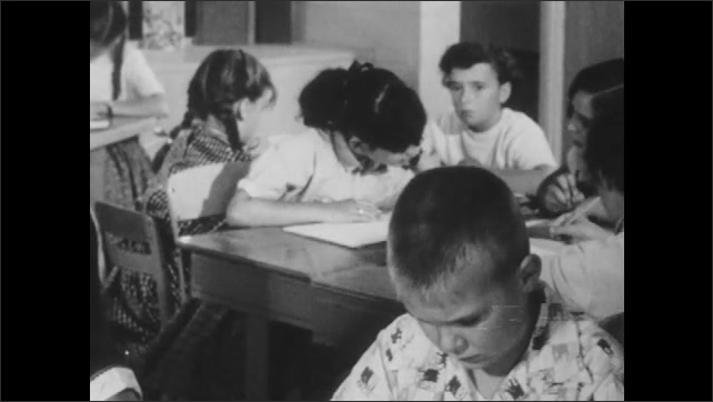 1950s: Students read books and work at tables in classroom. Teacher looks concerned. Teacher sits next to boy. Boy reads aloud.