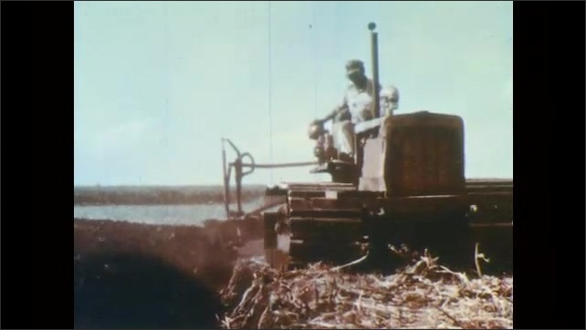 1960s: Water bubbling in reservoir. Hoses in reservoir, tilt up to field. Farm equipment drives toward camera. Equipment drives through soil. Equipment drives away from camera.